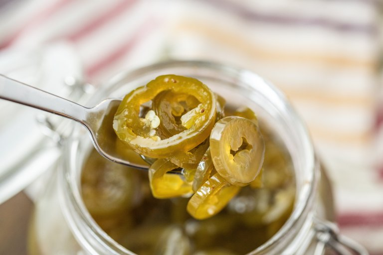 Candied Jalapenos being scooped out of a hinged mason jar